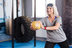 Delighted aged woman working out with a ball Stock Photo