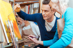 Delighted artist showing elderly woman how to paint. Good advisor. Delighted handsome young artist showing elderly women how to paint while holding a brush and royalty free stock photo