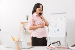 Delighted asian pregnant woman talking on smart phone Stock Photo