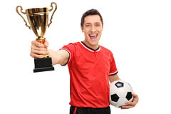 Delighted athlete holding a gold trophy. Delighted athlete holding a football and a gold trophy isolated on white background stock images