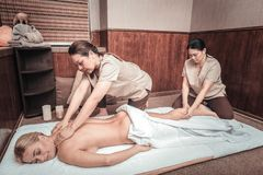 Delighted attractive young woman having aroma massage. So pleasurable. Delighted attractive women smiling while having aroma massage royalty free stock image