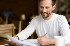 Delighted bearded man making notes in the cafe Royalty Free Stock Photography