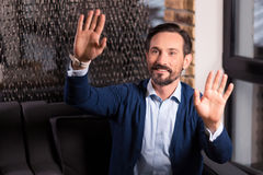 Delighted bearded man pressing his palms to the virtual screen Stock Photo
