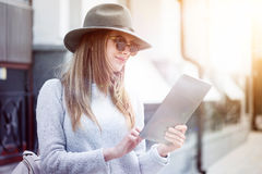 Delighted beautiful woman using tablet. Sunny days. Cheerful content young woman expressing gladness and smiling while using tablet stock photography