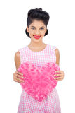 Delighted black hair model holding a pink heart shaped pillow Royalty Free Stock Image