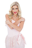 Delighted blonde model in pink dress posing holding her shoulder Royalty Free Stock Photo