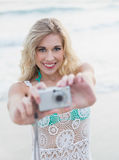Delighted blonde woman in white beach dress taking a picture Royalty Free Stock Photo