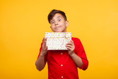 Delighted boy posing with giftbox. Small expressive kid holding giftbox and looking at camera on yellow background royalty free stock images