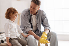 Delighted boy putting hand on the knee of his father. Listen to me. Attractive men sitting on the bench and putting on rubber gloves while looking at his son Stock Image