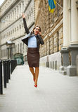 Delighted business woman jumping for joy while talking on the sm Stock Images