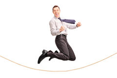 Delighted businessman jumping over a rope Royalty Free Stock Photo