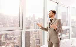 Delighted businessman standing in his office Stock Image