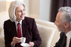 Delighted businesswoman having the conversation with her colleague Stock Image
