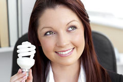 Delighted businesswoman holding a light bulb Stock Photo