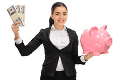 Delighted businesswoman holding money bundles and piggybank Stock Photo
