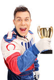 Delighted car racer holding a trophy Royalty Free Stock Image
