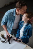 Delighted caring father kissing his daughter. I love you. Delighted caring pleasant father holding a gun and kissing his daughter while standing near her Royalty Free Stock Image