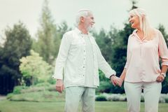 Delighted cheerful man holding his wifes hand stock image