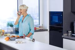 Delighted cheerful woman doing a phone call. Phone call. Delighted cheerful woman doing a phone call while standing in the kitchen royalty free stock photography