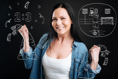 Delighted cheerful woman holding bags with money royalty free stock image