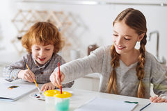 Delighted clever kids learning how to draw. Future artists. Amusing happy creative siblings having fun in the morning painting with watercolors while enjoying royalty free stock photography