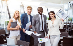 Delighted colleagues standing in the office. Positive mood. Delighted overjoyed colleagues standing in the office and smiling while expressing gladness stock images