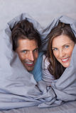 Delighted couple having fun wrapped in their duvet Royalty Free Stock Image