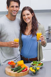 Delighted couple holding glass of orange juice Royalty Free Stock Image