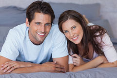 Delighted couple lying on bed Stock Photography