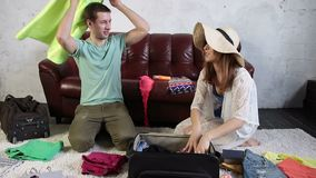 Delighted couple preparing for vacation at home Stock Images