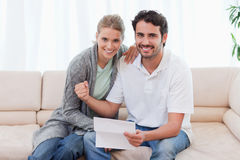 Delighted couple reading a letter Royalty Free Stock Image