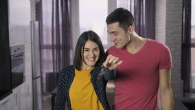 Delighted couple shaking keys and dancing. Portrait of delighted young couple standing in the house and shaking keys to new home at camera. Cheerful excited stock footage