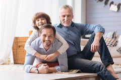 Delighted cute boy hugging his father. Care and support. Delighted cute happy boy lying on his fathers back and hugging him while having a great time with his Stock Photos