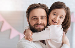 Delighted cute girl embracing her dad
