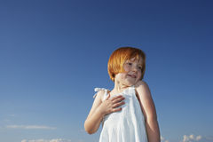 Delighted Cute Girl Looking Away Against Blue Sky Stock Photo
