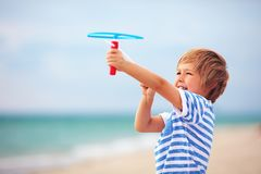 Delighted cute young boy, kid having fun on sandy beach, playing leisure activity games with propeller toy Stock Photo