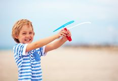 Delighted cute young boy, kid having fun on sandy beach, playing leisure activity games with propeller toy Stock Photography