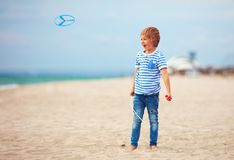 Delighted cute young boy, kid having fun on beach, playing with propeller toy Stock Photography