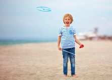 Delighted cute young boy, kid having fun on sandy beach, playing leisure activity games with propeller toy Stock Photos