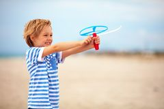 Delighted cute young boy, kid having fun on sandy beach, playing leisure activity games with propeller toy Stock Images