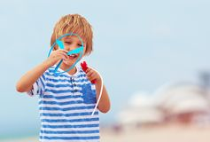 Delighted cute young boy, kid having fun on sandy beach, playing leisure activity games with propeller toy Royalty Free Stock Images