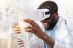 Delighted doctor looking at genome model. Exciting day. Close up of young delighted doctor using virtual glasses while looking at genome model and smiling stock photos