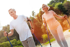 Delighted elderly couple practicing Nordic walking. Our hobby. Delighted nice elderly couple practicing Nordic walking and enjoying the activity while being stock photography