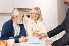 Delighted elderly couple signing agreement at home Royalty Free Stock Photos
