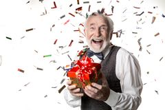 Delighted elderly male on celebration party. Happy birthday. Waist up portrait of cheerful pensioner with present in his hands expressing unbridled joy, colorful stock photos