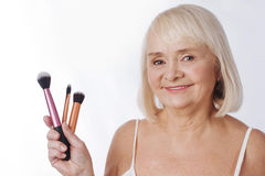 Delighted elderly woman holding cosmetic tools Stock Photography
