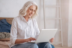 Delighted elderly woman holding a laptop. Being online. Delighted pleasant smart elderly woman holding a laptop and surfing the Internet while sitting on the bed royalty free stock photos