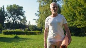 Delighted envelheceu o homem que anda no parque com uma esteira do exercício em suas mãos vídeos de arquivo