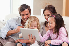 Delighted family using a tablet computer Stock Photos