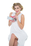 Delighted fashion blonde model opening a gift Royalty Free Stock Images
